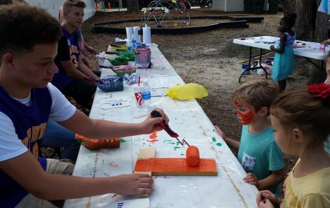 Basketball players worked the Kids Zone station helping put handprints on the fence downtown.