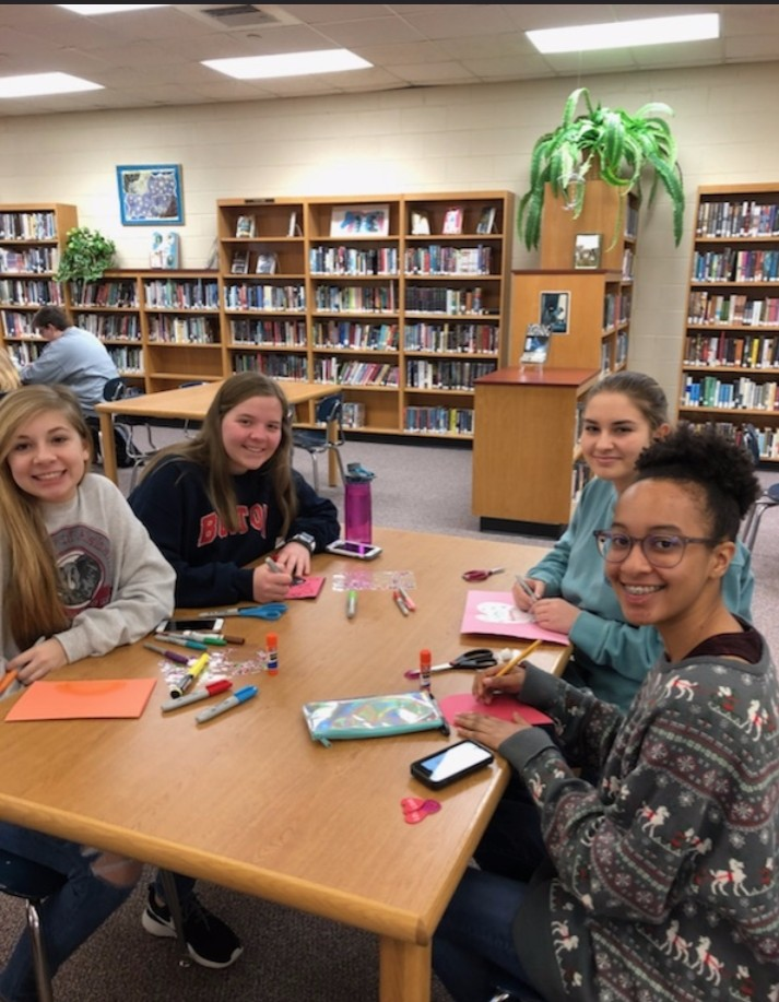 Jocelyn Wright, Savannah Weed, Lydia Walker, and Mallori Sanders make valentines for women and children.